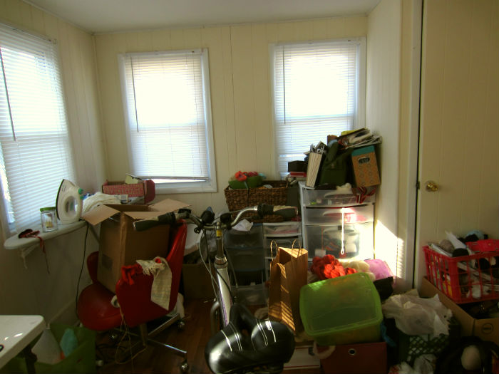 The other side of my studio, filled with badly stacked boxes, leaving just enough room for my bike and indoor trainer.